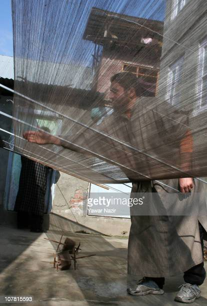 A Kashmiri artisan collects pashmina threads used to make a pashmina shawls at his workshop December 29 2010 on the outskirts of Srinagar the summer...