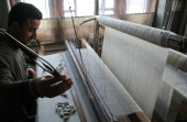 Kashmiri artisan works on a pashmina shawl with shuttle at his workshop December 29 2010 on the outskirts of Srinagar the summer capital of Indian...