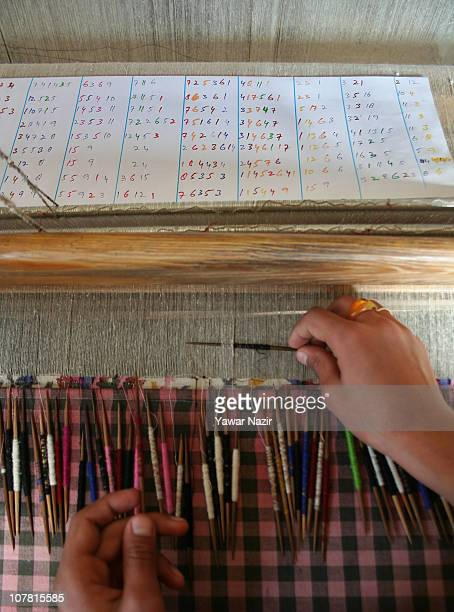 Kashmiri artisan works on a woven Kani or Jamewar shawl as he reads an inscription to design it at his workshop December 29 2010 on the outskirts of...