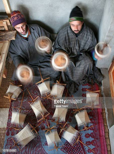 Kashmiri artisans collects pashmina threads on wheels used to make a pashmina shawls at their workshop December 29 2010 on the outskirts of Srinagar...