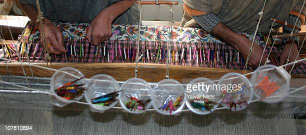 Kashmiri artisans work on a woven Kani or Jamewar shawl at their workshop on December 29 2010 in the outskirts of Srinagar the summer capital of...