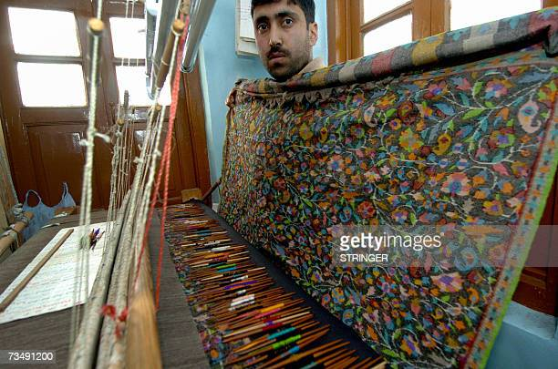 Kashmiri artisian Shabir Ahmed poses with a half woven Kani or Jamewar shawl at his workshop in Srinagar 05 March 2007 Some 150 tooji or small sticks...