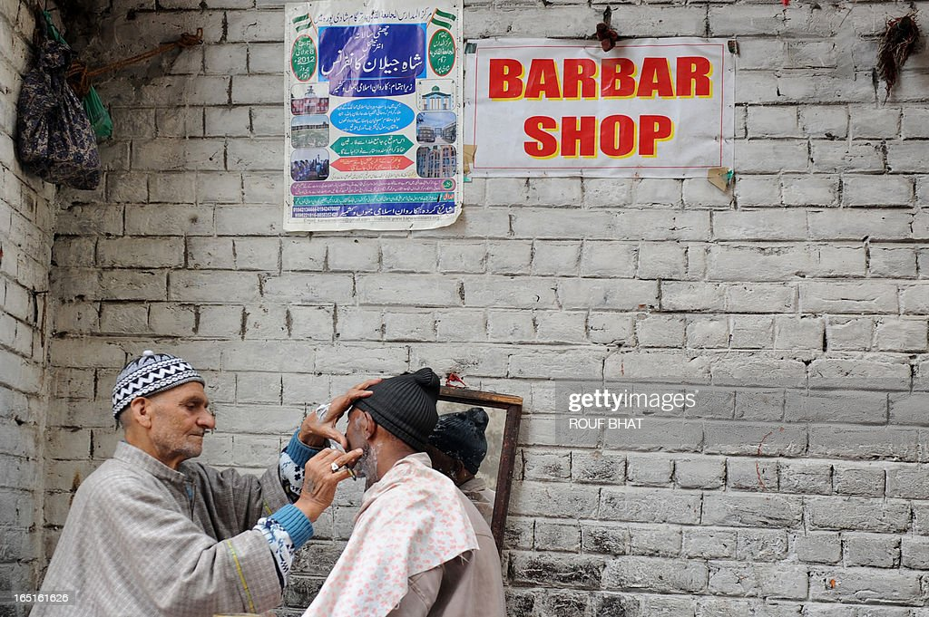 A Kashmiri barber shaves a customer at a roadside barber shop in Srinagar on April 1, 2013. Jammu and Kashmir's economy has taken a hit from the rash of strike calls given by separatists groups and curfew in the valley in the aftermath of the hanging of Parliament attack convict Afzal Guru. AFP PHOTO/Rouf BHAT