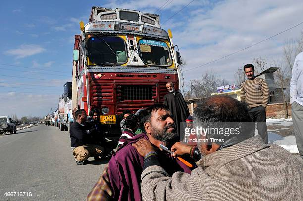 Kashmiri barber shaves a driver as their trucks are stranded at SrinagarJammu national highway due to land slide in Qazigund near Jawhar Tunnel on...