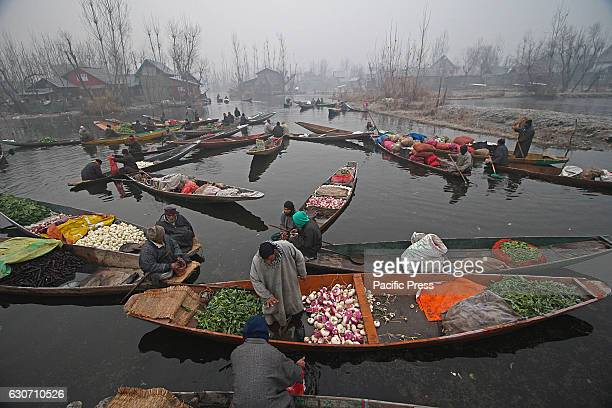 Kashmiri boatman attends a customer at the floating vegetable market in the interiors of famed Dal Lake in Srinagar the summer capital of Indian...
