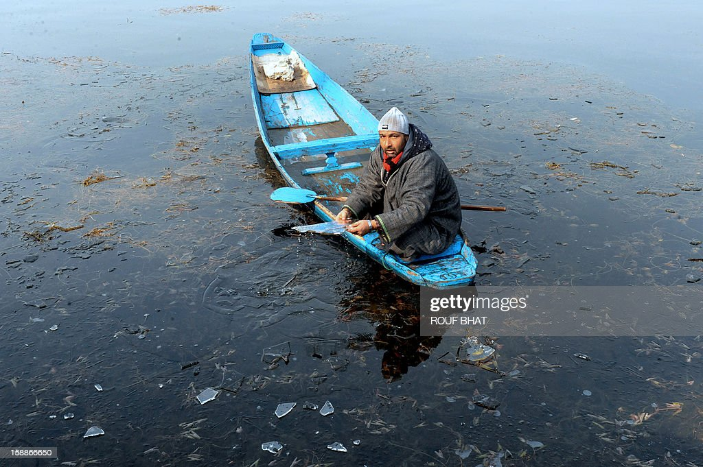 A Kashmiri boatman holds a piece of ice as he makes his way across Dal Lake in Srinagar on January 2, 2013. Thie Himalayan state of Jammu and Kashmir is in the midst of a 40-day spell of winter weather known locally as 'Chillai Kalan', during which the Kashmir Valley remains in the grip of extreme cold due to below-freezing nightime temperatures. AFP PHOTO/Rouf BHAT