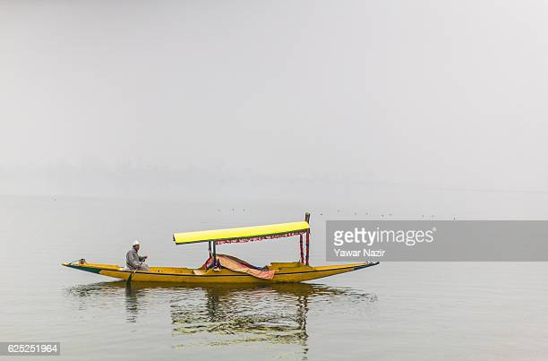 Kashmiri boatman rows his boat at the Dal lake during a cold foggy day on November 23 2016 in Srinagar the summer capital of Indian administered...