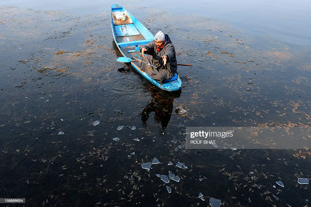 A Kashmiri boatman throws a piece of ice towards shore as he makes his way across Dal Lake in Srinagar on January 2, 2013. Thie Himalayan state of Jammu and Kashmir is in the midst of a 40-day spell of winter weather known locally as 'Chillai Kalan', during which the Kashmir Valley remains in the grip of extreme cold due to below-freezing nightime temperatures. AFP PHOTO/Rouf BHAT