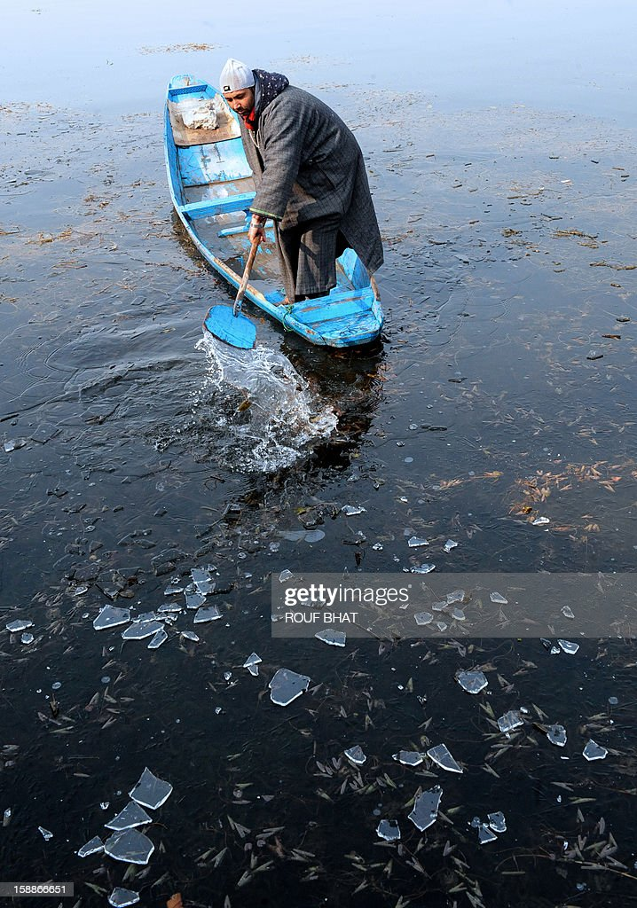 A Kashmiri boatman uses his oar to break through ice as he makes his way across Dal Lake in Srinagar on January 2, 2013. Thie Himalayan state of Jammu and Kashmir is in the midst of a 40-day spell of winter weather known locally as 'Chillai Kalan', during which the Kashmir Valley remains in the grip of extreme cold due to below-freezing nightime temperatures. AFP PHOTO/Rouf BHAT