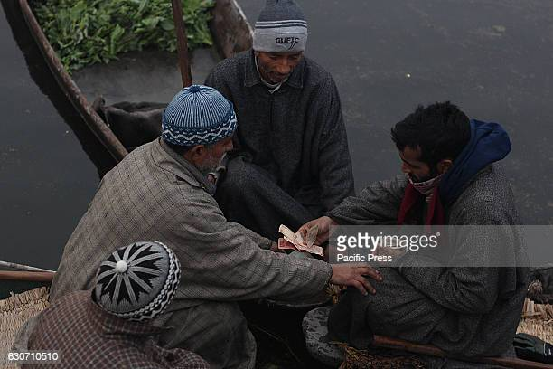 Kashmiri boatmen exchange currency notes after selling their produce at the floating vegetable market in the interiors of famed Dal Lake in Srinagar...