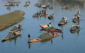 Kashmiri boatmen extract sand from the Jhelum river on the outskirts of Srinagar on February 12 2015 The construction of residential houses continues...