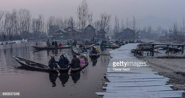 Kashmiri boatmen gather with their boats laden with vegetables in sub zero temperatures at the floating vegetable market in Dal Lake on December 26...