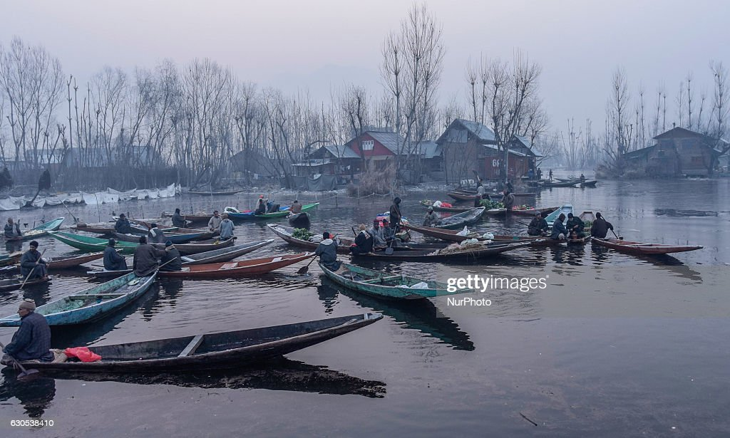 Kashmiri boatmen gather with their boats laden with vegetables ,in sub zero temperatures at the floating vegetable market in Dal Lake on December 26, 2016 in Srinagar, the summer capital of Indian administered Kashmir, India. The floating vegetable market, is active even in sub zero temperatures. Every morning Dal dwellers visit the market with their boats laden with vegetables that are later supplied to different parts of the city.