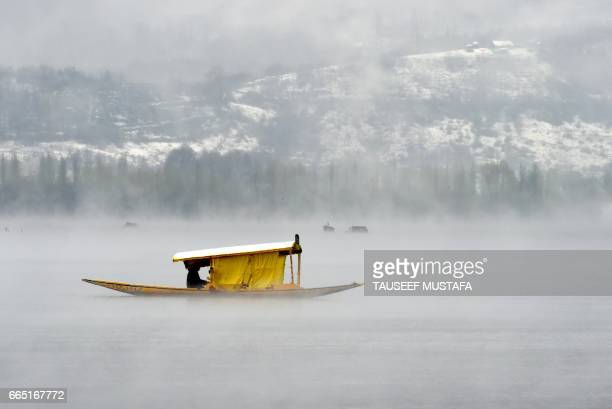 TOPSHOT Kashmiri boatmen paddle a shikara across Dal Lake amid dense fog following rainfall in Srinagar on April 6 2017 The SrinagarJammu National...