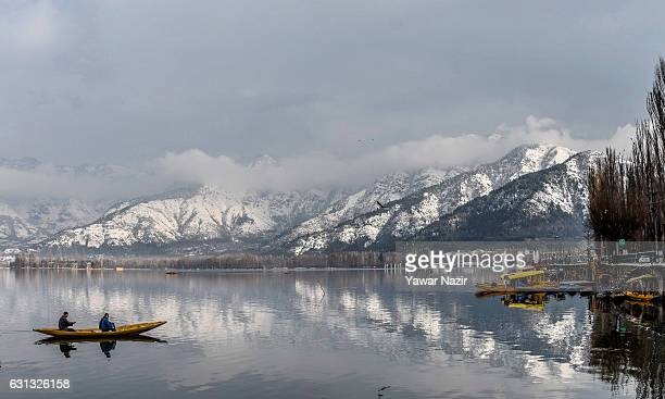 Kashmiri boatmen rows their boat as the snow covered Zabarvan mountain range is reflected on the waters of Dal Lake on January 09 2017 in Srinagar...