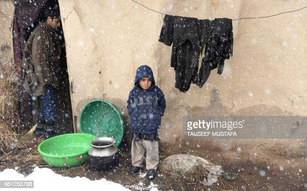 TOPSHOT Kashmiri boy looks on outside a his mud house on the outskirts of Srinagar during a fresh snowfall on March 102017 / AFP PHOTO / Tauseef...