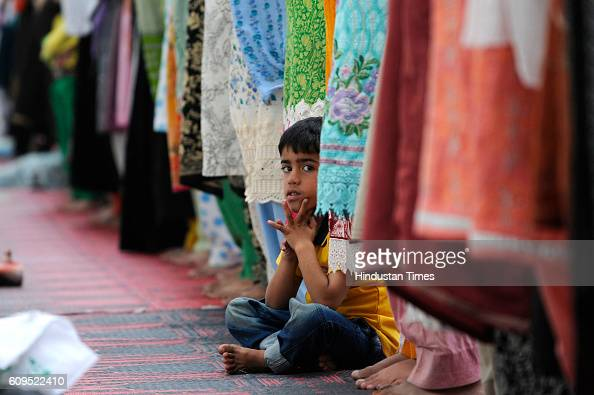Kashmiri boy looks up as Kashmiri women offer prayers at the Hazratbal Shrine on September 21 2016 in Srinagar India People are holding special...