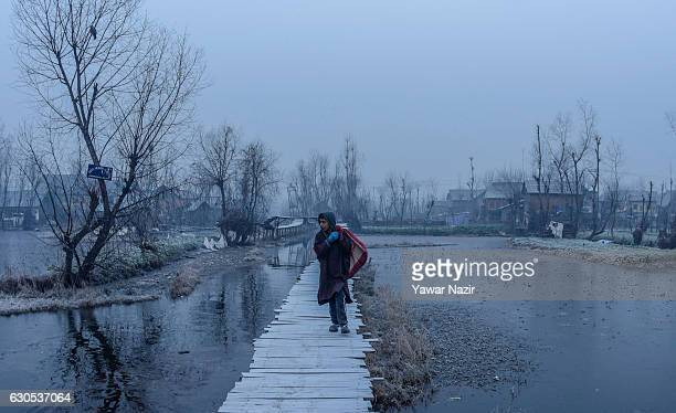 Kashmiri boy walks on a bridle path in sub zero temperatures at the floating vegetable market in Dal Lake on December 26 2016 in Srinagar the summer...