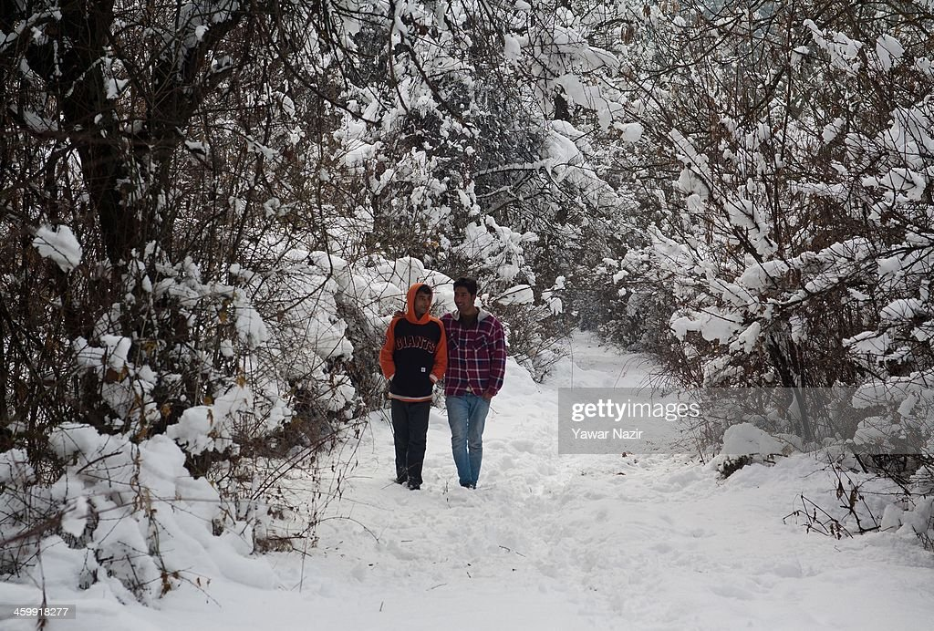 Kashmiri boys stroll in a snow covered park in a park on January 01, 2014 in Srinagar, the summer capital of Indian Administered Kashmir, India. Weather conditions have improved in Kashmir after a spell of heavy snowfall that had distrupted road and air traffic, cutting off the Valley from the rest of world .