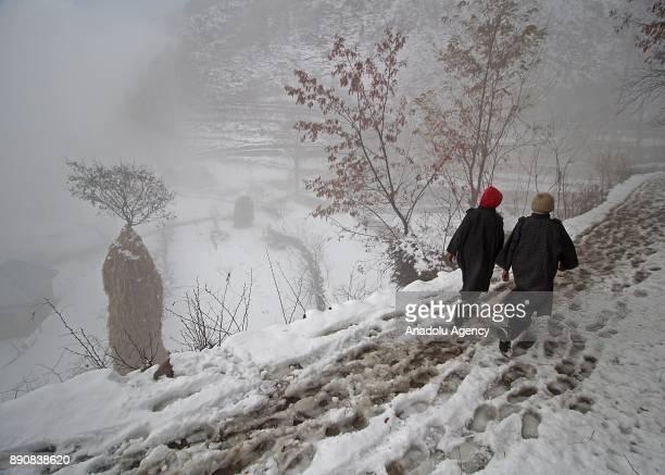 Kashmiri boys walk on the snow covered road as it snows in Srinagar the summer capital of Indian controlled Kashmir on December 12 2017Heavy snowfall...