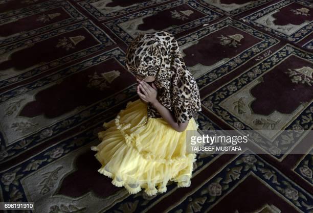 A Kashmiri child prays inside Kashmir's main mosque Jamia Masjid during Ramadan in downtown Srinagar on June 15 2017 Muslims around the world abstain...