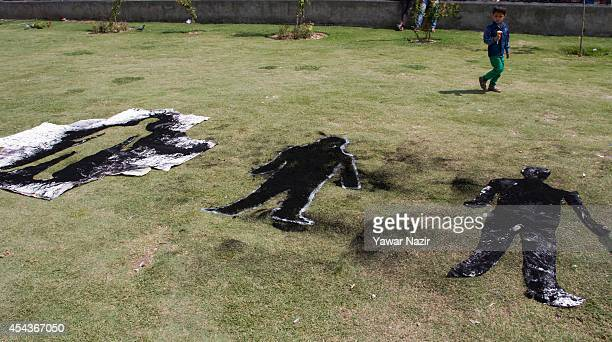 Kashmiri child walks past a mural left on the ground by the Kashmiri Muslim artists during a protest demonstration organised by Association of...