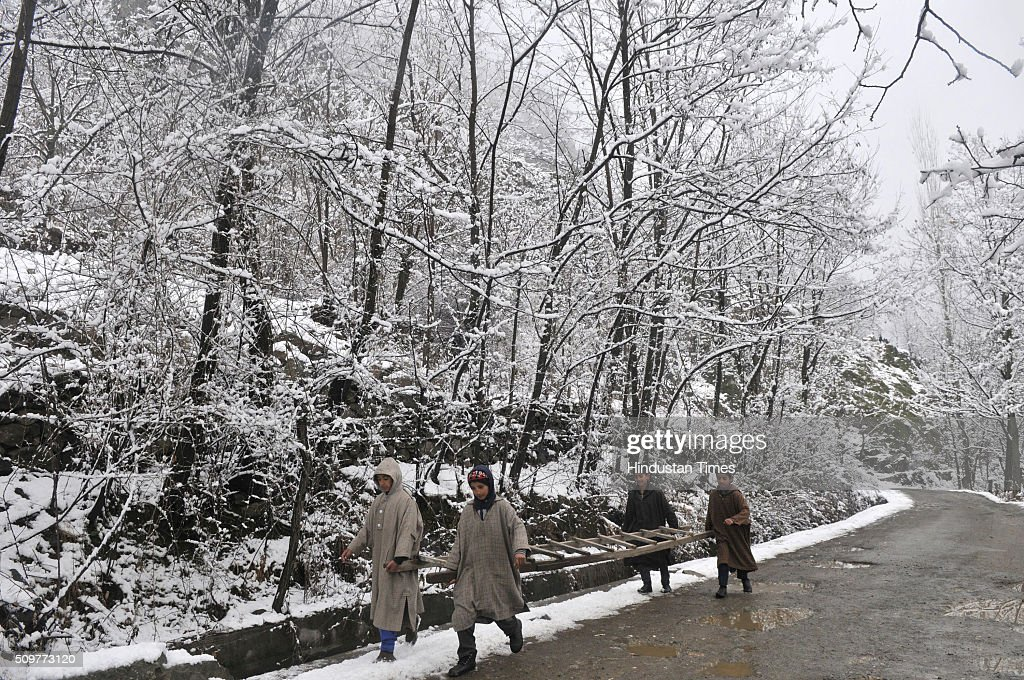 Kashmiri children carrying ladder a snow covered road on February 12, 2016 on the outskirts of Srinagar, India. Incessant snowfall and rains on Thursday led to the closure of the valleys arterial Srinagar-Jammu National Highway and brought relief from a long spell of dry weather in Kashmir.