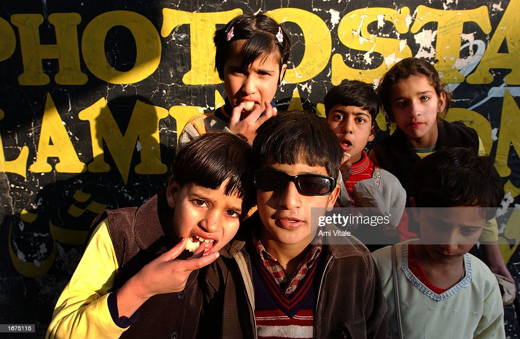 Kashmiri children eat sweets while enjoying the Islamic holiday of Eid-ul-Fitr December 6, 2002 in the summer capital of Srinagar in the Indian held state of Jammu and Kashmir. The Islamic holiday of Eid-ul-Fitr is a day which culminates the Muslim month of fasting for Ramadan.