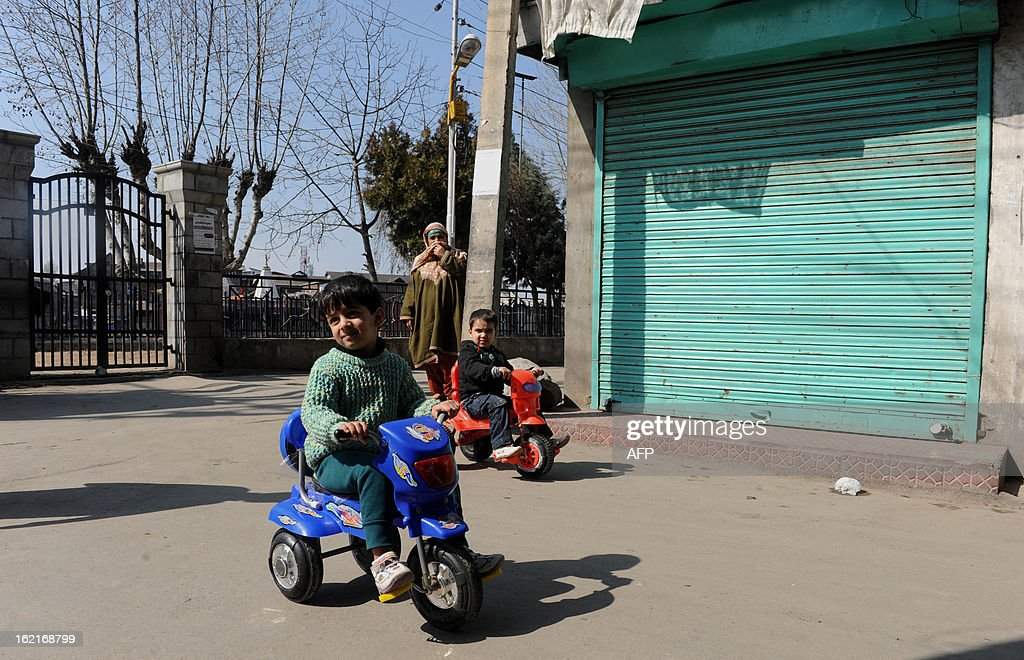 Kashmiri children pedal past closed shops during a shutdown in Srinagar on February 20, 2013. A separatist alliance, All Parties Hurriayt Conference, opposed to Indian rule in Kashmir called for a two-day strike in to press the demanded for return of Afzal Guru's mortal remains to his family. Guru was executed on February 9, 2013 and buried inside a high security prison in New Delhi after he was convicted of his role in a deadly attack on Indian parliament in 2001. AFP PHOTO/ Rouf BHAT