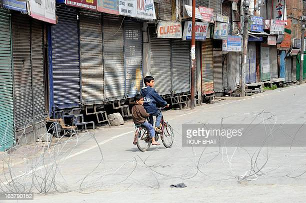 Kashmiri children pedal past closed shops during the third day of a curfew imposed on the Kashmiri summer capital in Srinagar on March 16 2013...