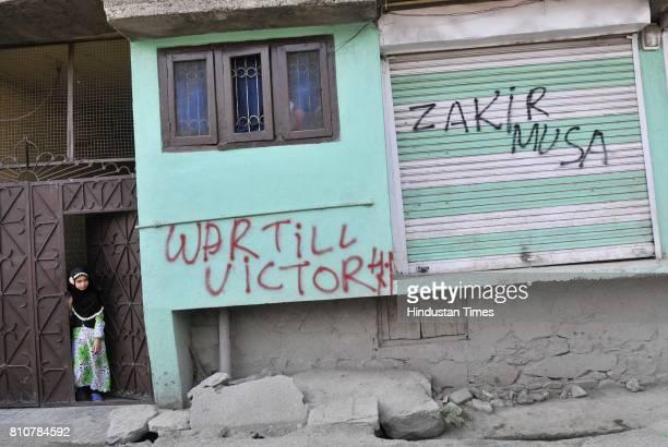 Kashmiri children stand next to graffiti that reads War till Victory and a militant commander Zakir Musa during curfew in Lal Chowk area on July 8...