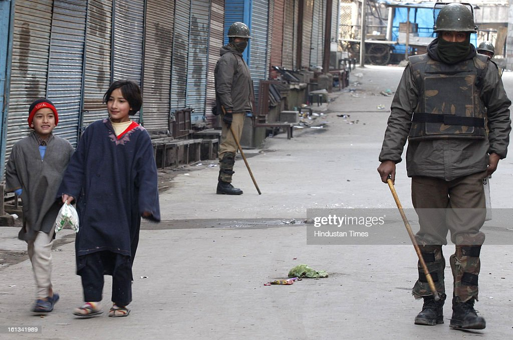 Kashmiri childrens are walking on deserted street after the parliament attack convict, Muhammad Afzal Guru was hanged in New Delhi, during Second day curfew on February 10, 2013 in Srinagar, India. Guru, who was found guilty of conspiring and sheltering the militants who attacked Parliament on December 13, 2001 in which nine people were killed, was buried in the prison premises as per the jail manual.