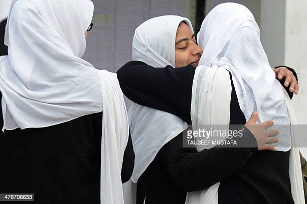 Kashmiri college students embrace as they gather for classes on the first day of the schooling session at Women's College in Srinagar on March 5 2014...
