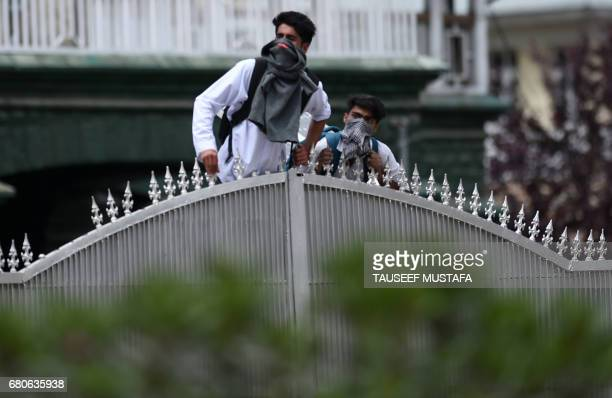 Kashmiri college students look on during clashes between students and Indian government forces in central Srinagar's Lal Chowk on May 9 2017 Police...