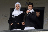 Kashmiri college students look on while another blows bubble gum as they gather for classes on the first day of the schooling session at Women's...