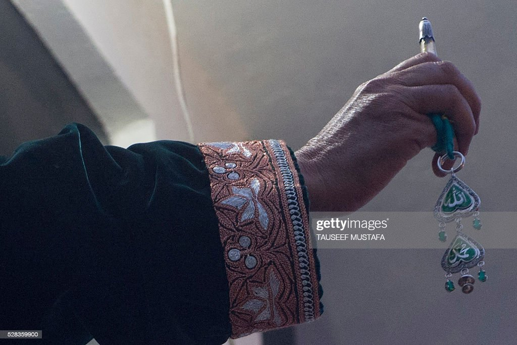 A Kashmiri custodian displays a holy relic, believed to be a hair from the Prophet Muhammad's beard, during celebrations for Miraj-Ul-Alam (ascension to heaven) at Kashmir's main Hazratbal Shrine in Srinagar on May 5, 2016. Thousands of Muslims converge annually for celebrations at the shrine near the summer capital of the state of Jammu and Kashmir. / AFP / TAUSEEF