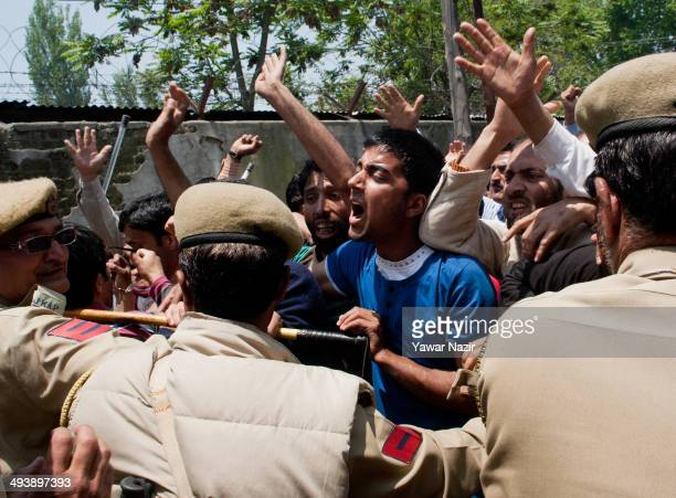 Kashmiri daily wagers shout slogans as they scuffle with Indian police during a protest on May 26 2014 in Srinagar the summer capital of Indian...