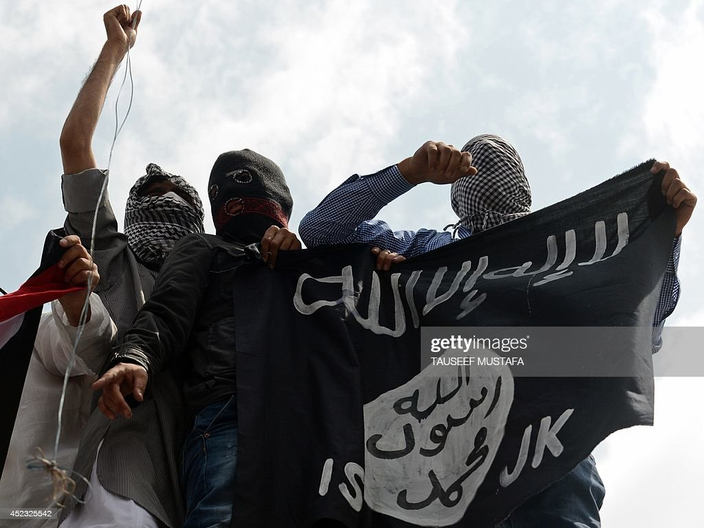 Kashmiri demonstrators hold up a flag of the Islamic State of Iraq and the Levant during a demonstration against Israeli military operations in Gaza...