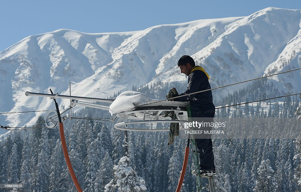 A Kashmiri electrician adjusts an electric wire in Gulmarg, about 55 kms north of Srinagar, on December 13, 2012. Gulmarg is the main ski destination in Indian Kashmir and hundreds of foreigners visit the slopes despite an ongoing insurgency in the region. AFP PHOTO/ Tauseef MUSTAFA