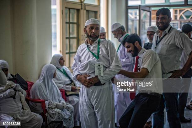 Kashmiri employee helps a Hajj pilgrim to tie his belt before departing for the annual Hajj pilgrimage on July 26 2017 in Srinagar the summer capital...