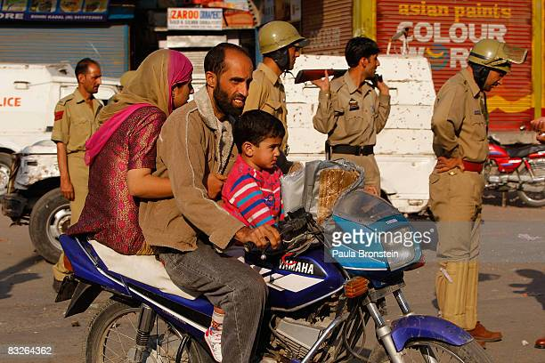 Kashmiri family ride a motorcycle past Indian police as they direct traffic away from local street violence on October 13 2008 in Srinagar Kashmir In...