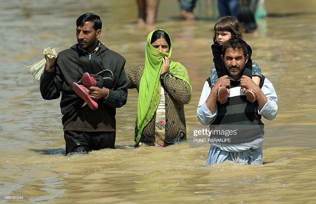 A Kashmiri family walks through the floodwaters in Srinagar on September 10 2014 Anger mounted over the slow pace of rescue operations in Indian...