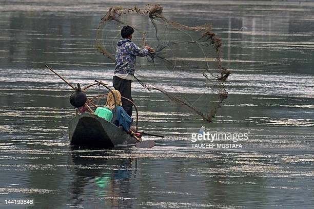 A Kashmiri fisherman casts his net into the Dal Lake during a windy and rainy day in Srinagar on May 11 2012 Pakistan said that it would host the...