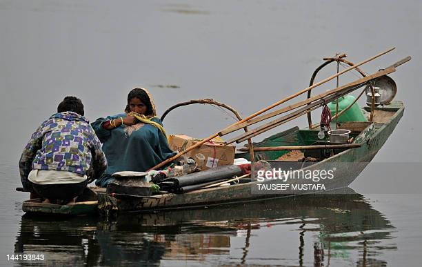 A Kashmiri fisherman rides his boat in the Dal Lake during a windy and rainy day in Srinagar on May 11 2012 Pakistan said that it would host the next...