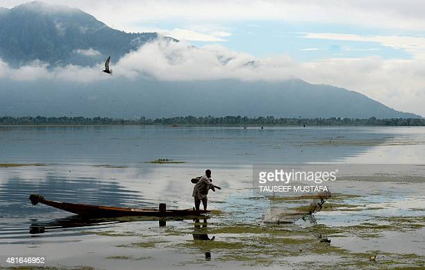 A Kashmiri fisherman throws a net into Dal Lake after heavy rainfall in Srinagar on July 23 2015 AFP PHOTO/Tauseef MUSTAFA