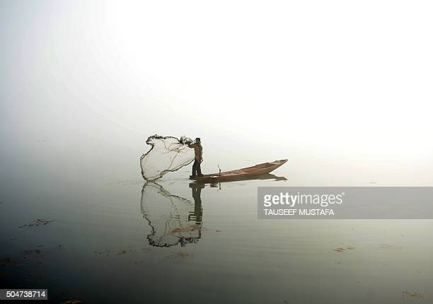 Kashmiri fisherman throws out his net from his boat on Dal lake during dense fog in Srinagar on January 13 2016 / AFP / TAUSEEF MUSTAFA