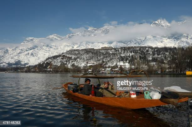 Kashmiri fishermen drink tea on a boat in Dal Lake following a snowfall in Srinagar on March 12 2014 Avalanches triggered by unusually heavy snowfall...