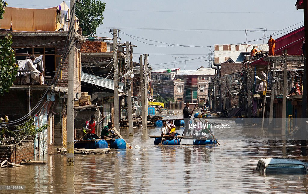 Kashmiri flood victims rows their makeshift rafts past submerged houses in the Bemina area on September 15 2014 in Srinagar the summer capital of...