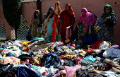 Kashmiri flooded victim women choose leftout cloths in a Mosque where the flooded victims have taken refuge on September 13 2014 in Srinagar the...