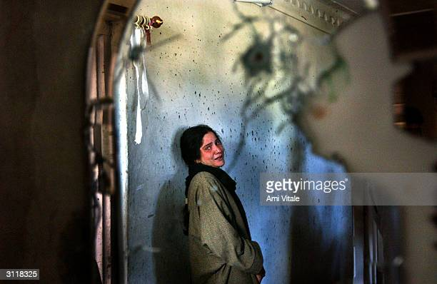 Kashmiri girl cries inside her house that was completely destroyed after Indian army soldiers and separatist militants holed up inside it were...